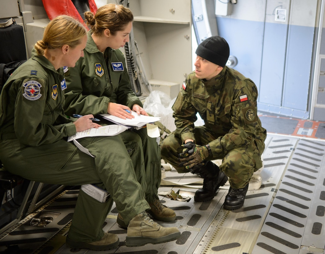 Polish Air Force 2nd Lt. Andrzej Nartonowicz, an aeromedical evacuation doctor, listens to two 86th Aeromedical Evacuation Squadron Airmen as they prepare for a mock mission Dec. 3, 2015, at Ramstein Air Base, Germany. The 86th AES and other aeromedical evacuation specialists on Ramstein showcased procedures and tactics used to save lives for the developing Polish AE mission. (U.S. Air Force photo/Staff Sgt. Armando A. Schwier-Morales)