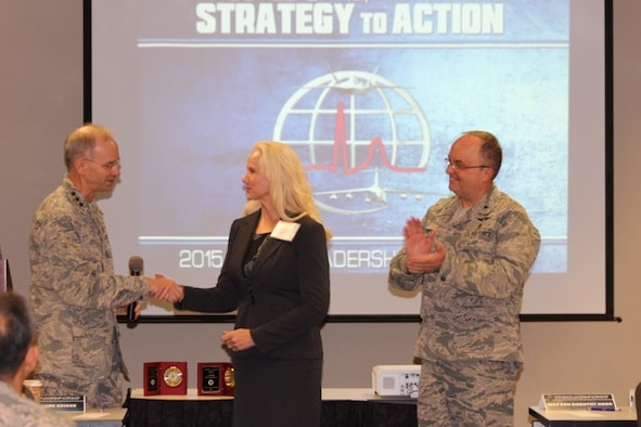 Air Force Surgeon Lt. Gen. Mark Ediger congratulates Senior Historian Judith Taylor for the two awards earned by the Air Force Medical Services History Office at the 2015 Senior Leadership Workshop in Leesburg, Va., on Nov. 16. Brig. Gen (Dr.) Lee Payne, the commander of Air Force Medical Operations Agency at Lackland Air Force Base, Texas, applauds on the right. (Photo Credit: Kevin M. Hymel, AFMS)