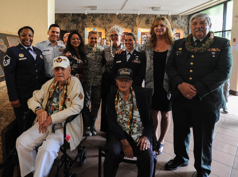 """U.S. Air Force Airmen from Pacific Air Forces take a photo with (front left to right) former U.S. Army Air Forces Durward Swanson and retired U.S. Air Force Col. Andrew Kowalski, Hickam Field attack survivors, and retired U.S. Army Maj. Wynn Warner, whose father raised the Hickam Flag before the attacks on Pearl Harbor and Hickam, after a ceremony, Dec. 7, 2015, Joint Base Pearl Harbor-Hickam, Hawaii. The ceremony was held to unveil the new flag case """"Old Glory"""" is to be displayed in. (U.S. Air Force photo by Tech. Sgt. Amanda Dick/Released)"""