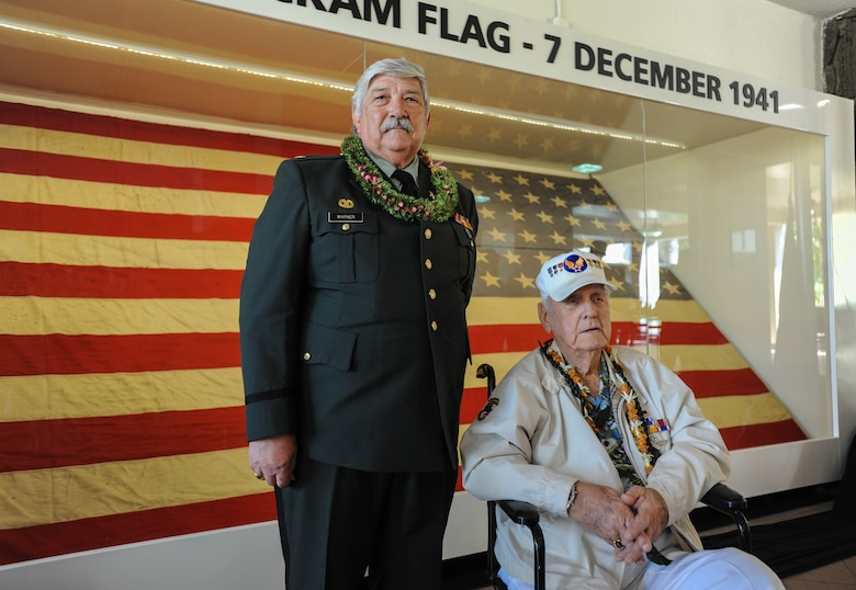 """(Left to right) Retired U.S. Army Maj. Wynn Warner and former U.S. Army Air Forces Tech. Sgt. Durward Swanson, Hickam Field attack survior, take a photo with """"Old Glory"""" after a ceremony, Dec. 7, 2015, Joint Base Pearl Harbor-Hickam, Hawaii. Warner's father, U.S. Army Air Forces Sgt. Tracy Warner, raised the flag Dec. 7, 1941, and Swanson lowered it the night after the attacks. (U.S. Air Force photo by Tech. Sgt. Amanda Dick/Released)"""