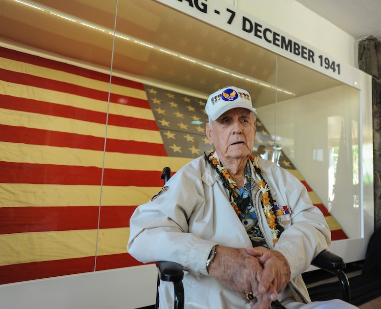 """Former U.S. Army Air Forces Tech. Sgt. Durward Swanson, Pearl Harbor-Hickam Field attack survivor, takes a photo with the """"Hickam Flag"""" after a ceremony, Dec. 7, 2015, Joint Base Pearl Harbor-Hickam, Hawaii. Swanson, along with a fellow Airman, lowered the """"Hickam Flag"""" after the attacks Dec. 7, 1941, when they noticed it was still flying at night. (U.S. Air Force photo by Tech. Sgt. Amanda Dick/Released)"""