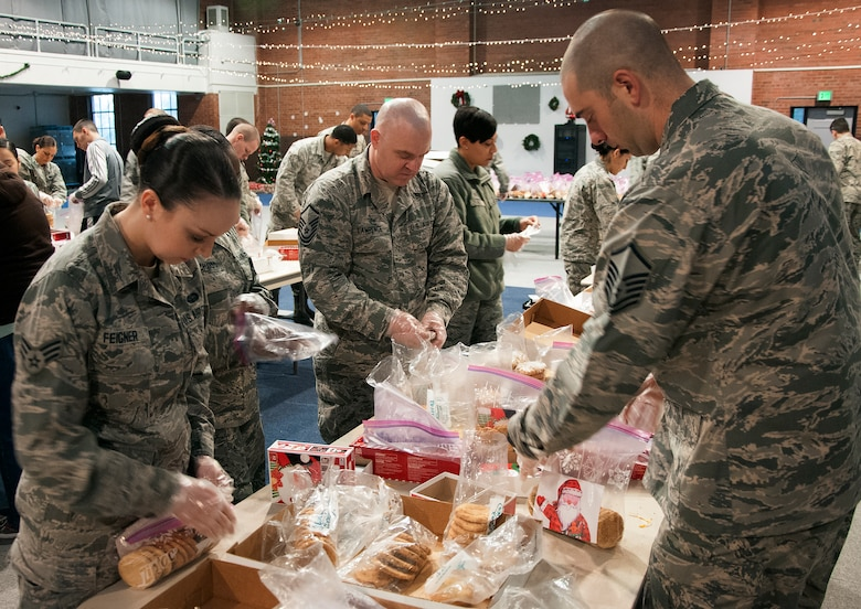 Volunteers make cookie bags for Airmen Dec. 7, 2015, inside the Fall Hall Community Center on F.E. Warren Air Force Base, Wyo. Each bag consisted of 12 cookies and a card wishing Airmen living in the dorms a happy holiday. (U.S. Air Force photo by Senior Airman Brandon Valle)