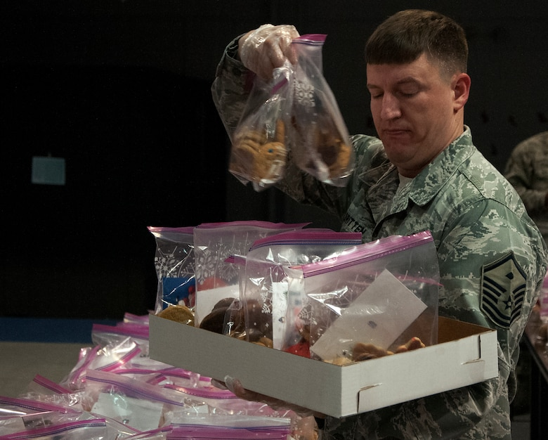 Master Sgt. Jeremy Britten, 620th Ground Combat Training Squadron first sergeant, organizes bags of cookies into boxes Dec. 7, 2015, inside the Fall Hall Community Center on F.E. Warren Air Force Base, Wyo. Each bag was delivered to the rooms of Airmen living in the dorms. (U.S. Air Force photo by Senior Airman Brandon Valle)