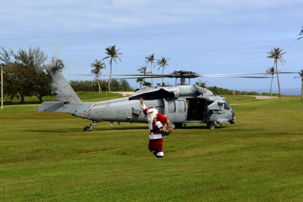 Santa Claus waves to Andersen families after landing on a helicopter during the children's holiday party Dec. 5, 2015, at Andersen Air Force Base, Guam. Helicopter Sea Combat Squadron 25 aviators gave Santa a ride so he could visit Andersen's children this holiday season. (U.S. Air Force photo/Airman 1st Class Alexa Ann Henderson)
