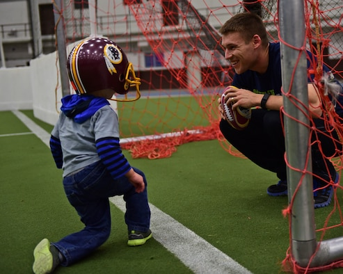 Staff Sgt. Chris Meyer, 28th Contracting Squadron contract administrator, celebrates a touchdown with his son, Nate, while playing football in the Pride Hangar at Ellsworth Air Force Base, S.D., Nov. 4, 2015. Meyer and his family use the facility during winter months to escape inclement weather. (U.S. Air Force photo by Airman 1st Class James L. Miller/Released)