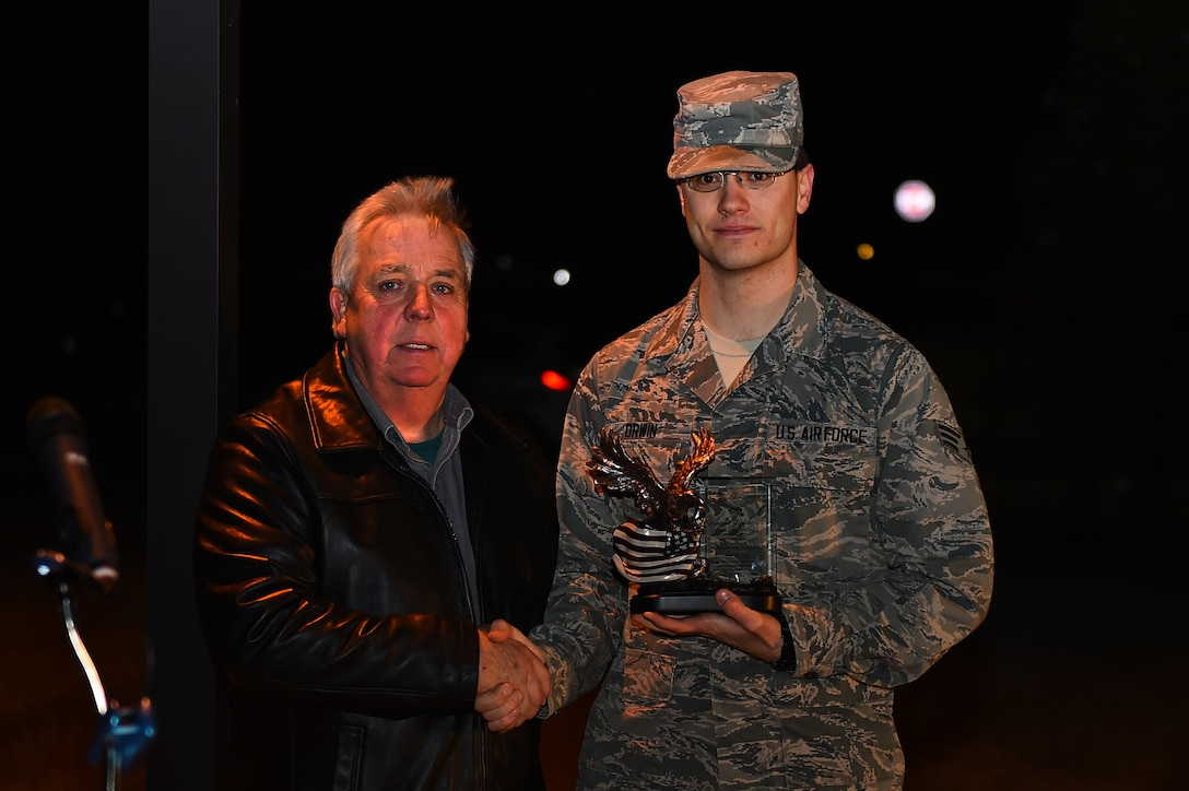 Senior Airman Christopher Orwin, 460th Operations Group Detachment 45 satellite operations technician, receives the Kristopher Mansfield award from Craig Mansfield during a tree-lighting ceremony Dec. 3, 2015, on Buckley Air Force Base, Colo. The ceremony takes place every year to honor Senior Airman Kristopher Mansfield, who was killed in a drunk driving accident in 2004. (U.S. Air Force photo by Airman First Class Gabrielle Spradling/Released)