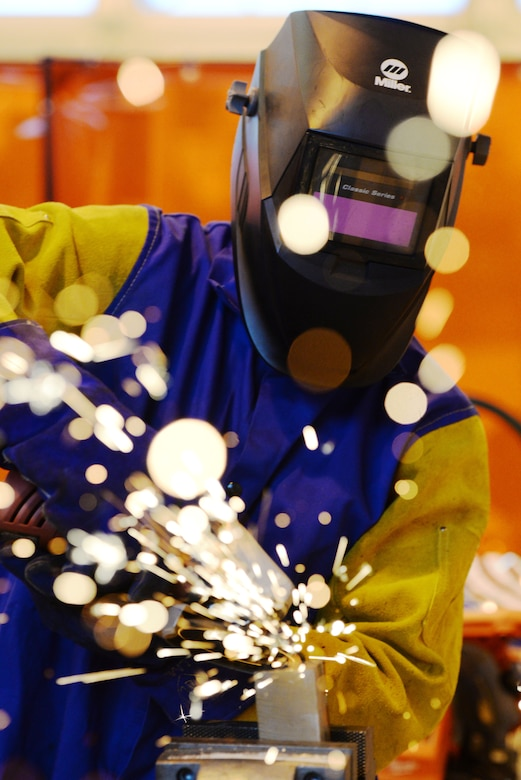 A welder with the Rapid Development Integration Facility grinds down some metal while working on a project inside their 20,000 square-foot manufacturing and modification facility at Wright-Patterson Air Force Base, Ohio, Dec. 2, 2015. Since their start, the RDIF has has been able to successfully return more than $150 million to their customers who could then use that money on additional projects. Additionally, they have been able to help their customers realize more than 70 percent cost savings and schedule time. (U.S. Air Force photo/Wesley Farnsworth.)