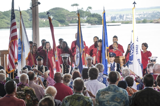 Members of U.S. Pacific Command's joint service color guard present the colors as Melamai Kapu'uwaimai Choir members sing the national anthem during the Pearl Harbor Day Commemoration Anniversary at Joint Base Pearl Harbor-Hickam, Hawaii, Dec. 7, 2015. U.S. Air Force photo by Staff Sgt. Christopher Hubenthal