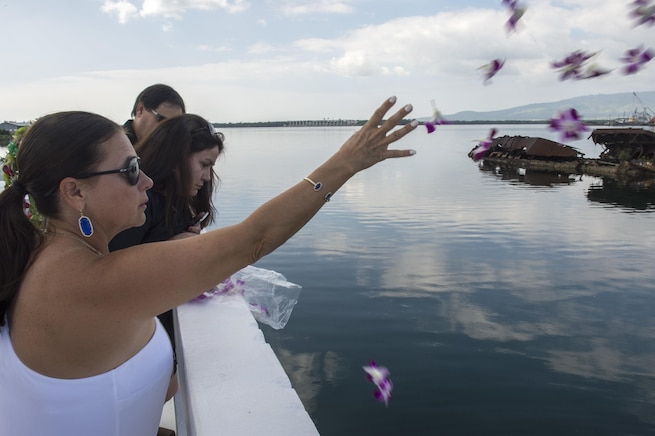 Jeannette Siciliani, daughter of retired Navy Chief boatswain's mate Donald Show, a USS Phoenix survivor, throws flowers during an ash-scattering ceremony at the USS Utah Memorial during the Pearl Harbor Day commemoration anniversary at Joint Base Pearl Harbor-Hickam, Hawaii, Dec. 7, 2015. U.S. Navy photo by Petty Officer 3rd Class Katarzyna Kobiljak