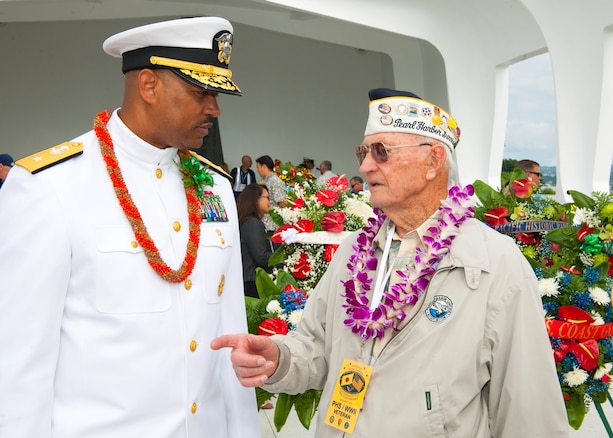 Navy Rear Adm. John Fuller, left, commander, Navy Region Hawaii and Naval Surface Group Middle Pacific, speaks with Ed Schuler, a survivor of the attacks on Pearl Harbor during a wreath dedication ceremony on Joint Base Pearl Harbor-Hickam, Hawaii, Dec. 7, 2015. U.S. Navy photo by Petty Officer 2nd Class Jeff Troutman