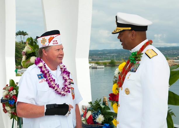 Veteran of Foreign Wars member Joseph Bragg, left, speaks with Navy Rear Adm. John Fuller, commander, Navy Region Hawaii and Naval Surface Group Middle Pacific, during a wreath dedication ceremony in remembrance of the Pearl Harbor attack, on Joint Base Pearl Harbor-Hickam, Hawaii, Dec. 7, 2015. U.S. Navy photo by Petty Officer 2nd Class Jeff Troutman