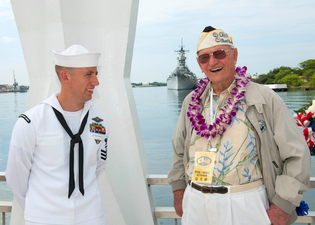 Ed Schuler, who survived the attacks on Pearl Harbor, Dec. 7, 1941, talks with a sailor during a wreath dedication ceremony in remembrance of the attacks 74 years ago, on Joint Base Pearl Harbor-Hickam, Hawaii, Dec. 7, 2015. U.S. Navy photo by Petty Officer 2nd Class Jeff Troutman