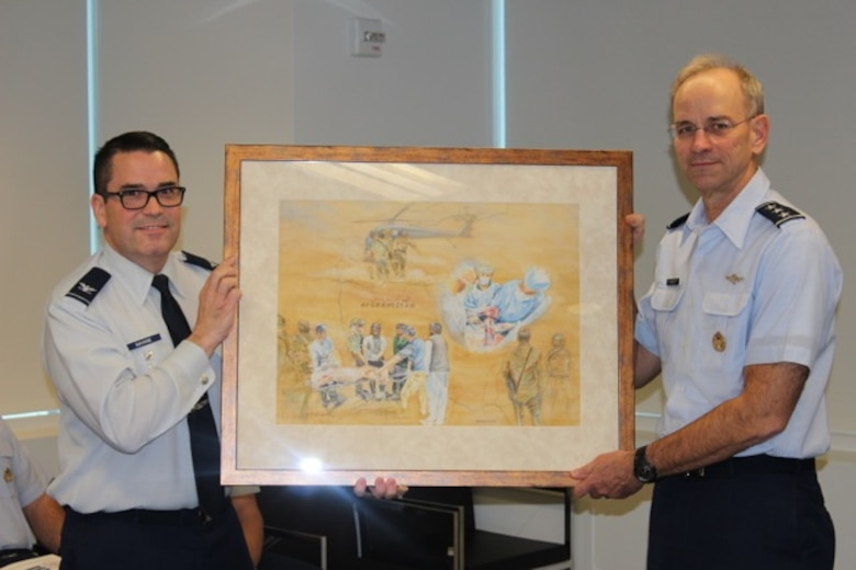 Col. John Savage and Lt. Gen. Mark Ediger display Ms. Judy Blomquist's painting which depicts AFMS medics in Afghanistan rendering aid after a bombing. The painting was presentedat a ceremony at the DHHQ in Falls Church, Va., on Nov. 27..