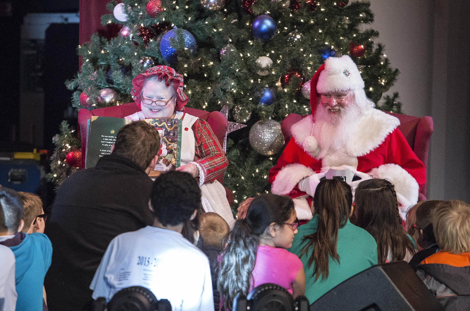 Santa and Mrs. Clause display a childrens book while United States Air Force Band of the West perform holiday music during the Holiday in Blue concert Dec. 7, 2015 at the Edgewood Independent School District Theatre for the Performing Arts in San Antonio, Texas. The concert included a variety of holiday songs from around the world, a children's story and a sing-a-long. Attendees included members of JBSA, community members and retirees. The Airmen assigned to the band are highly-trained professional musicians who have dedicated themselves to serving their country through music. (U.S. Air Force photo by Johnny Saldivar)