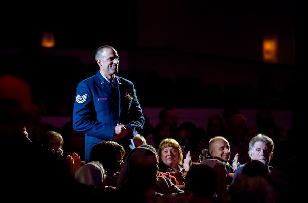 Tech. Sgt. Scott Liddick, 66th Training Squadron Survival, Evasion, Resistance, and Escape specialist, is applauded for his contributions to the U.S. Air Force during the Holiday in Blue concert Dec. 7, 2015 at the Edgewood Independent School District Theatre for the Performing Arts in San Antonio, Texas. The concert included a variety of holiday songs from around the world, a children's story and a sing-a-long. Attendees included members of JBSA, community members and retirees. The Airmen assigned to the band are highly-trained professional musicians who have dedicated themselves to serving their country through music. (U.S. Air Force photo by Johnny Saldivar)