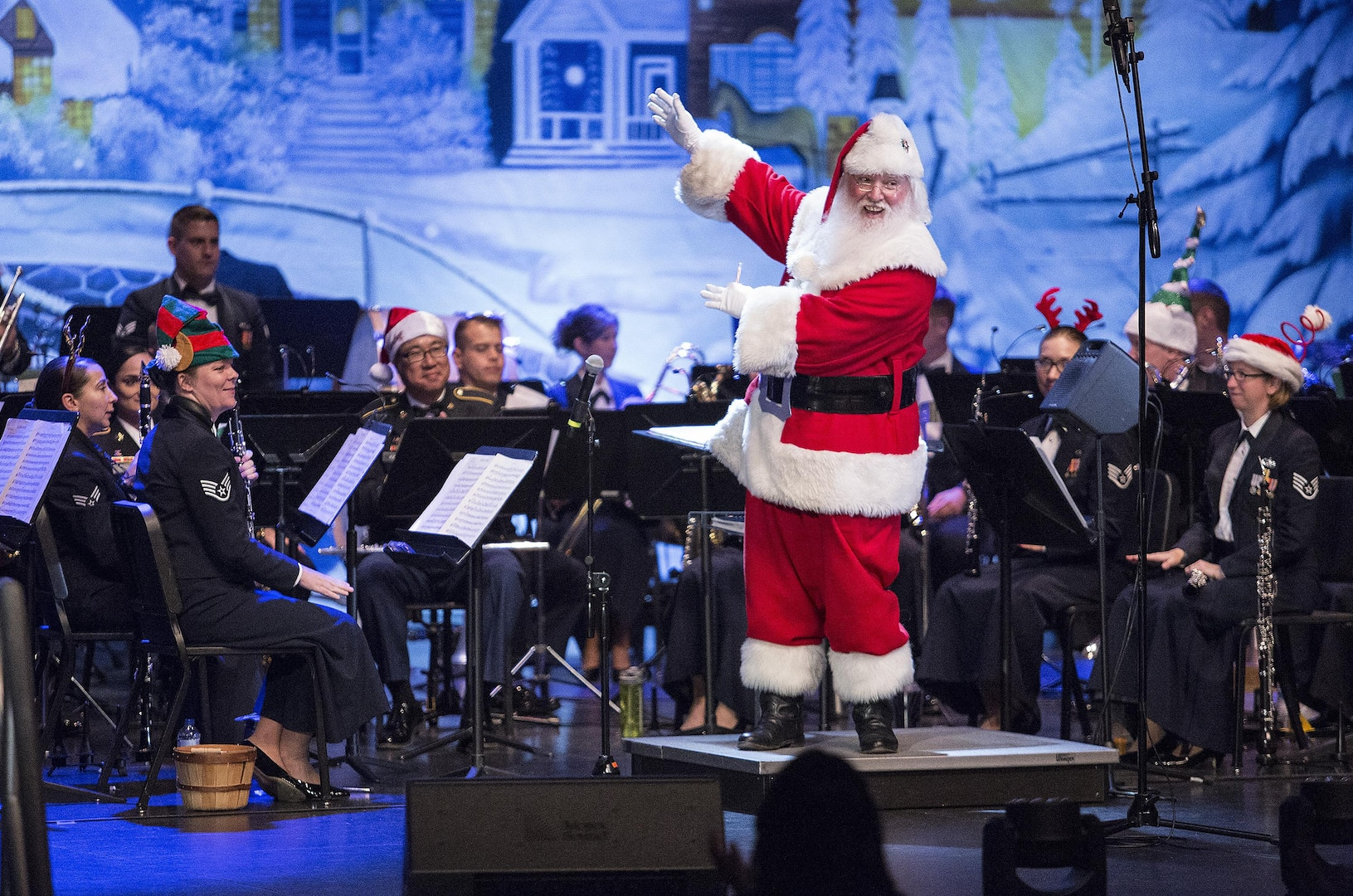 Santa Clause presents members of the USAF Band of the West during the Holiday in Blue concert Dec. 7, 2015 at the Edgewood Independent School District Theatre for the Performing Arts in San Antonio, Texas. The concert included a variety of holiday songs from around the world, a children's story and a sing-a-long. Attendees included members of JBSA, community members and retirees. The Airmen assigned to the band are highly-trained professional musicians who have dedicated themselves to serving their country through music. (U.S. Air Force photo by Johnny Saldivar)