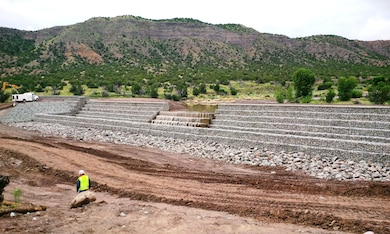 "SANTA CLARA PUEBLO, N.M. – Water flows over the partially-constructed ""structure 1"" July 30, 2015. The structure is part of the advanced measures the District is building to help protect the Pueblo from flash flooding. Photo by Mike Goodrich."