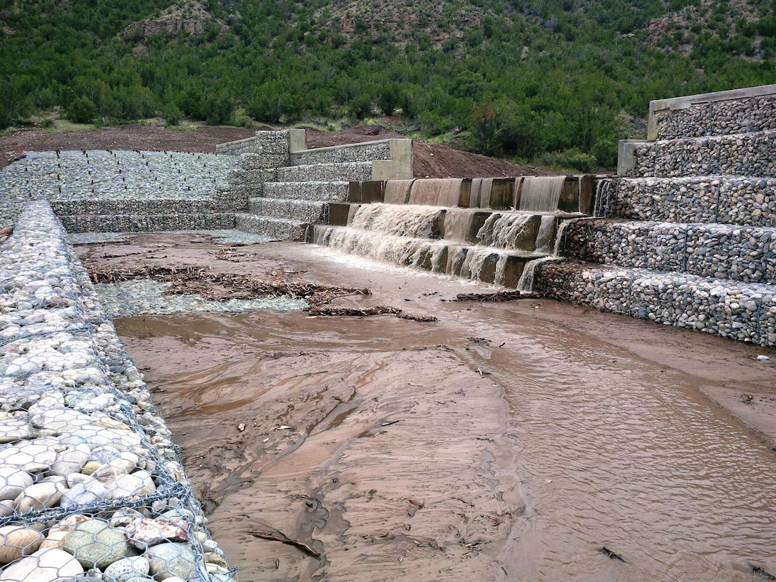 "SANTA CLARA PUEBLO, N.M. – Water flows over the partially-constructed ""structure 2"" July 30, 2015.  The structure is part of the advanced measures the District is building to help protect the Pueblo from flash flooding. Photo by Mike Goodrich. This was a 2015 photo drive entry."