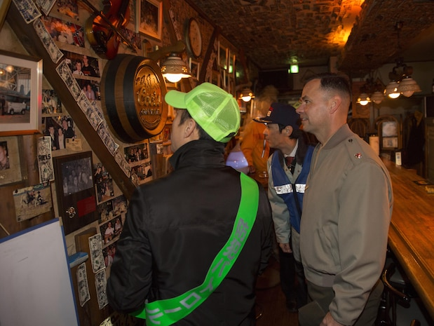 Lt. Col. Gary Thomason, executive officer of Marine Corps Air Station Iwakuni, Japan, and Iwakuni City officials visit a local restaurant in downtown Iwakuni during the 6th Joint Leadership Walk Dec. 4, 2015. The Joint Leadership Walk, led by Yoshihiko Fukuda, mayor of Iwakuni City, walked participants through the streets of Iwakuni engaging local citizens and service members in the community. The leadership walk represents the unique relationship between the air station and Iwakuni City.