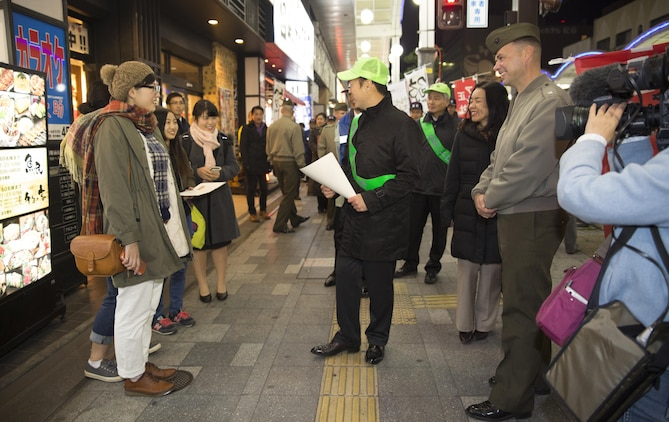 Lt. Col. Gary Thomason, executive officer of Marine Corps Air Station Iwakuni, Japan, and Iwakuni City officials engage with local Japanese citizens during the 6th Joint Leadership Walk in Iwakuni Dec. 4, 2015. Yoshihiko Fukuda, mayor of Iwakuni City, led participants through the city to foster the unique and long lasting relationship between the air station and Iwakuni City.