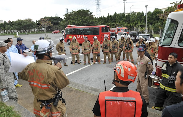 Yasuaki Nakama, Okinawa City Fire Department captain, briefs a training plan to Okinawa City Fire Department and Kadena Fire Department crew members during a bilateral hazardous materials training exercise, Dec. 8, 2015, at the Okinawa City Civic Center, Japan. The Kadena Fire Department and Okinawa City Fire Department trained together to build proficiency and understanding with each other. (U.S. Air Force photo by Naoto Anazawa)