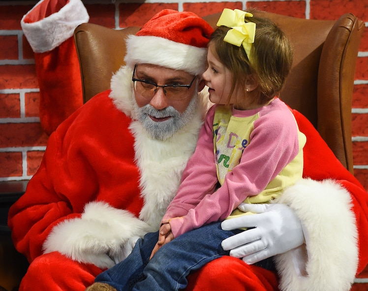 Brooklyn Houghton, 4, whispers into Santa's ear as he listens to what she wants for Christmas this year. Brooklyn, the daughter of Julie and Staff Sgt. Eric Houghton, Air Force Global Strike Command missile engineering office got the chance to visit with Santa Dec. 4, 2015, following the F.E. Warren Air Force Base, Wyo., annual tree lighting ceremony. (U.S. Air Force photo by R.J. Oriez.)