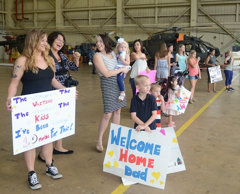 Families, friends and loved ones welcome home Sailors from the Helicopter Sea Combat Squadron 25's Detachment 1 after a seven month deployment Dec. 8, 2015, at Andersen Air Force Base, Guam. Two detachments from the squadron deployed to support operations aboard U.S. Navy vessels and shore based locations in the Pacific theater. (U.S. Air Force photo by Airman 1st Class Arielle Vasquez/Released)