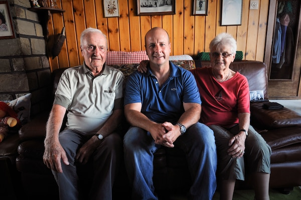 From left, Gaston Mean, an Awyaille, Belgium, resident for more than 70 years, sits with U.S. Air Force Chief Master Sgt. James McCloskey, and Mean's wife, in the living room of the Belgian home of the Mean family, Aug. 12, 2015.