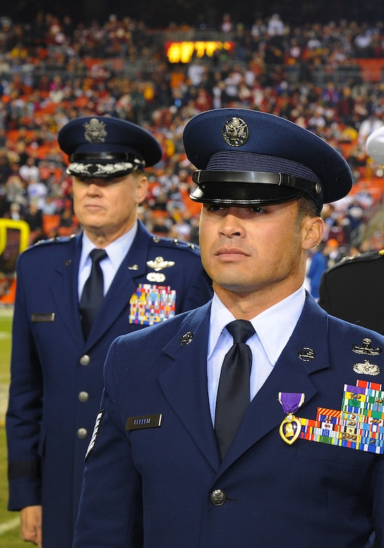 Technical Sgt. Christopher Ferrell, 11th Civil Engineer Squadron's Explosive Ordnance Disposal flight, is honored for his Purple Heart Medal by Maj. Gen. Darryl Burke, Air Force District of Washington commander, during an NFL half-time show of the Washington Redskins versus Dallas Cowboys game, Dec. 7, 2015. Ferrell was wounded while disarming a road-side bomb in Afghanistan in 2009. The ceremony was part of the Washington Redskins' annual Salute to Service game which honors the nation's veterans and active duty military. (U.S. Air Force photo by James E. Lotz/RELEASED).