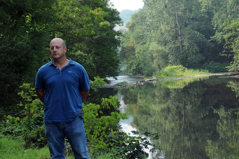 U.S. Air Force Chief Master Sgt. James McCloskey stands along the banks of the Ambleve River near Aywaille, Belgium Aug. 12, 2015. The location is where the fuselage of his great uncle, 1st Lt. Cuno Vernal Becker's B-17 Flying Fortress, tail number 4337569, crashed after a dogfight on Dec. 24, 1944. (U.S. Air National Guard photo by Senior Airman Shane S. Karp / released)