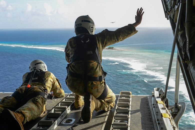 Australian Army Cpl. Teome Matamua and Sgt. Phillip McIllvaney, 176th Air Dispatch Squadron loadmasters, wave to islanders in the Federated States of Micronesia from the back of a C-130J Super Hercules after delivering donated goods and critical supplies to the islanders Dec. 8, 2015, during Operation Christmas Drop. The 2015 Christmas Drop missions marked the first time the event included trilateral air support from the Japan Air Self-Defense Force and RAAF. (U.S. Air Force photo/Staff Sgt. Katrina Brisbin)