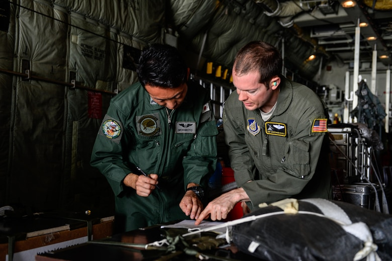 Japan Air Self-Defense Force Tech. Sgt. Satoshi Marimoto, left, and U.S. Air Force Tech. Sgt. Christopher Nichols, both C-130 loadmasters, review load documents before Operation Christmas Drop flight SANTA12 Dec. 8, 2015, at Andersen Air Force Base, Guam. The 2015 Christmas Drop missions marked the first time the event included trilateral air support from the JASDF and Royal Australian Air Force. (U.S. Air Force photo/Staff Sgt. Alexander W. Riedel)