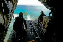 Australian Army Cpl. Teome Matamua and Sgt. Phillip McIllvaney, 176th Air Dispatch Squadron loadmasters, deliver the first low-cost, low-altitude bundle of Operation Christmas Drop 2015 to the island of Mogmog, Dec. 8, 2015. Australian and Japanese C-130 Hercules aircrews for the first time joined U.S. Airmen during the 64th year of Operation Christmas Drop which provided critical supplies to 56 islands throughout the Commonwealth of the Northern Marianas Islands, Federated States of Micronesia and Republic of Palau. It highlighted the U.S. and allied airpower capabilities to orient and respond to activities in peacetime and crisis. (U.S. Air Force photo/Staff Sgt. Katrina Brisbin)