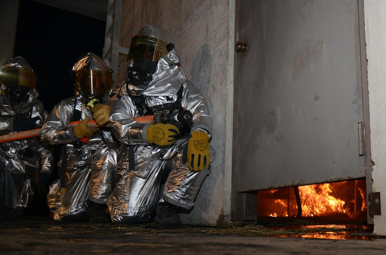 Firefighters from the 47th Civil Engineer Squadron prepare to enter the fire-training structure on Laughlin Air Force Base, Texas, Nov. 18, 2015. The training consisted of a first-floor fire and involved practicing multiple techniques. (U.S. Air Force photo by Airman 1st Class Brandon May)