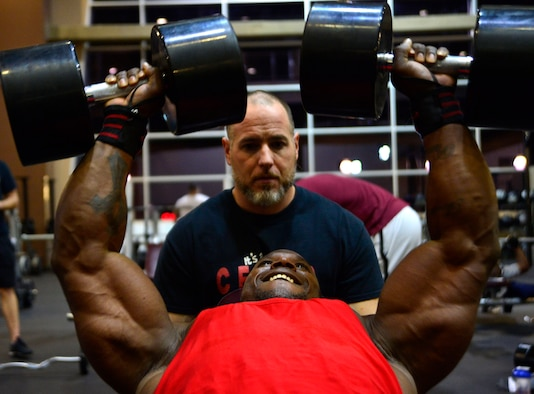Tech. Sgt. David, a 432nd Maintenance Group contract officer representative, performs chest fly repetitions while his trainer, Derrick Chandler, motivates him during a workout Dec. 4, 2015, at Nellis Air Force Base, Nevada. David recently attained his International Federation of Bodybuilding and Fitness professional card, which allows him to compete in professional bodybuilding competitions. (U.S. Air Force photo/Airman 1st Class Christian Clausen)