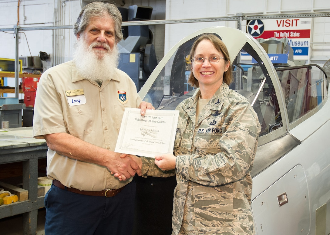 "88th Air Base Wing Vice Commander Col. Elena M. Oberg (right) presented Englewood resident Larry Youngblood with the Team Wright-Patt ""Volunteer of the Quarter"" award for the third quarter of 2015 on Dec. 9, 2015. (U.S. Air Force photo)"