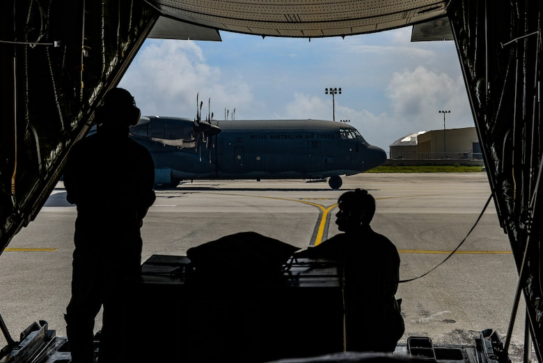Japanese Master Sgt. Toyonaga Toshihisa, left, and Tech. Sgt. Takahashi Tetsuki, both loadmasters with the Japanese Air Self-Defense Force 1st Tactical Airlift Wing, watch as a Royal Australian Air Force C-130J Hercules taxis along the flightline Dec. 8, 2015, at Andersen Air Force Base, Guam. The 64th year of Christmas Drop, which began in 1952, marked the first time international aviators from Japan and Australia joined the humanitarian airdrop mission. (U.S. Air Force photo/Staff Sgt. Alexander W. Riedel)