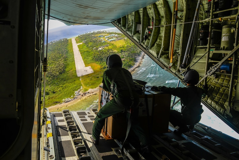 Japanese Air Self-Defense Force Master Sgt. Toyonaga Toshihisa, left, and Tech. Sgt. Takahashi Tetsuki's, both 1st Tactical Airlift Wing loadmasters,  look over the landing zone on the remote Micronesian island of Asor from the back of a C-130 Hercules Dec. 8, 2015, during Operation Christmas Drop. The 2015 Christmas Drop missions mark the first time the event includes trilateral air support from the JASDF and Royal Australian Air Force. (U.S. Air Force photo/Staff Sgt. Alexander Riedel)