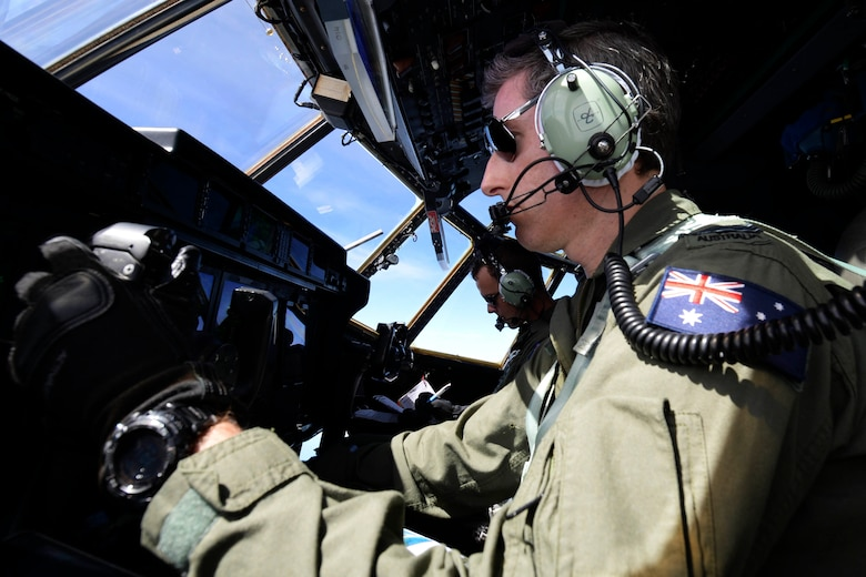 Flying Officer Brendon Carraro, a Royal Australian Air Force C-130J Hercules copilot, takes control of a C-130J Hercules Dec. 8, 2015, during Operation Christmas Drop. This is the first time U.S. allies and international partners from Japan and Australia trained for Humanitarian Aid/Disaster Relief with the U.S. Air Force while providing critical supplies to 56 Micronesian islands impacting approximately 20,000 people covering 1,000 by 1,800 nautical miles of operating area. (U.S. Air Force photo/Staff Sgt. Katrina Brisbin)