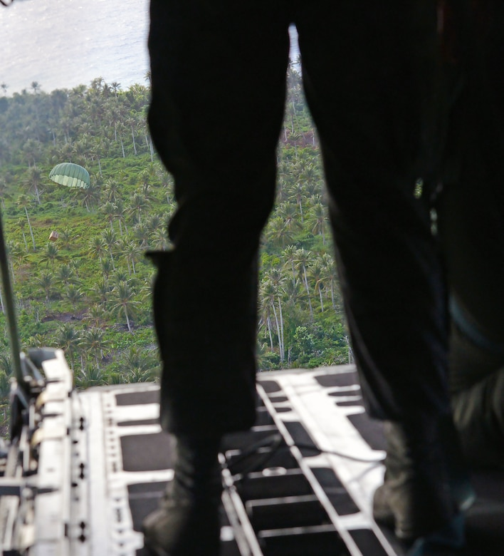 Loadmasters from the 36th Airlift Squadron, Yokota Air Base, watch a low-cost low-altitude bundle filled with donated goods and supplies drop onto the island of Fais from the back of a C-130H during Operation Christmas Drop, Dec. 8, 2015. This is the first trilateral Operation Christmas Drop where the U.S. Air Force, Japan Air Self-Defense Force and the Royal Australian Air Force work together to provide critical supplies to 56 Micronesian islands impacting 20,000 islanders covering 1,000 by 1,800 nautical miles. (U.S. Air Force photo by Tech. Sgt. Melissa K. Mekpongsatorn)