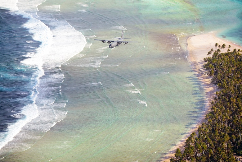 A Royal Australian Air Force C-130J flies over the Federated States of Micronesia during Operation Christmas Drop, Dec. 8, 2015. The RAAF dropped the first official bundle to the island of MogMog during the first trilateral execution of the training mission alongside Japanese Air Self-Defense Force and U.S. Air Force. Operation Christmas Drop is a humanitarian aid/disaster relief training event where C-130 crews provide critical supplies to 56 islands throughout the Commonwealth of the Northern Marianas, Federated States of  Micronesia and Republic of Palau. (U.S. Air Force photo by Tech. Sgt. Melissa K. Mekpongsatorn)