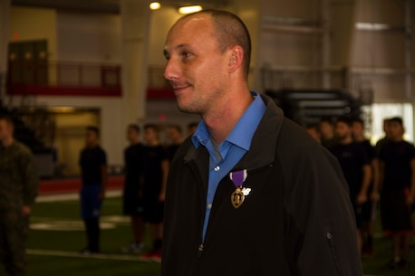 Darren D. Minder, a former Marine Corps sergeant, awaits to be dismissed after receiving the Purple Heart inside the Saginaw Valley State University Field House, Dec. 5, 2015. Darren received the Purple Heart medal for sustaining an enemy gunshot wound to the abdomen while on a patrol during his deployment to Habbinyah, Iraq, as a corporal, Oct. 4, 2006.
