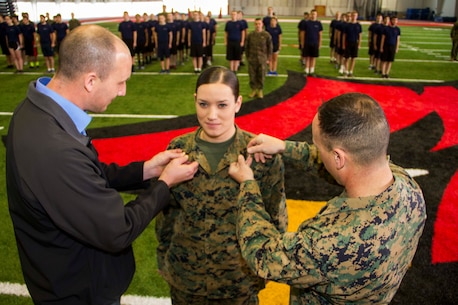 Leah J. Minder, middle, a Marine Corps recruiter in Mt. Pleasant, Mich., receives a promotion to staff sergeant inside the Saginaw Valley State University Field House, Dec. 5, 2015. Minder's rank is pinned to her collars by 1stSgt Todd Braun, right, Alpha Company I-I, 1st battalion 24th Marines, 25th regiment, 4th Marine Division, first sergeant in Grand Rapids, Mich., and her husband, Darren D. Minder, left, former Marine Corps sergeant and Purple Heart medal recipient.