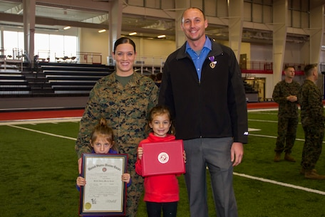 Staff Sgt. Leah J. Minder, left, a Marine recruiter in Mt. Pleasant, Mich., and her husband, Darren D. Minder, right, former Marine Corps sergeant and Purple Heart recipient, stand with their daughters, Jordan, left, and Addison after their combined promotion and Purple Heart ceremony inside the Saginaw Valley State University Field House, Dec. 5, 2015. Staff Sergeant Minder was promoted to the rank of staff sergeant and Darren received his Purple Heart medal for sustaining an enemy gunshot wound to the abdomen on a patrol, while deployed to Habbinyah, Iraq, as a corporal, Oct. 4, 2006.