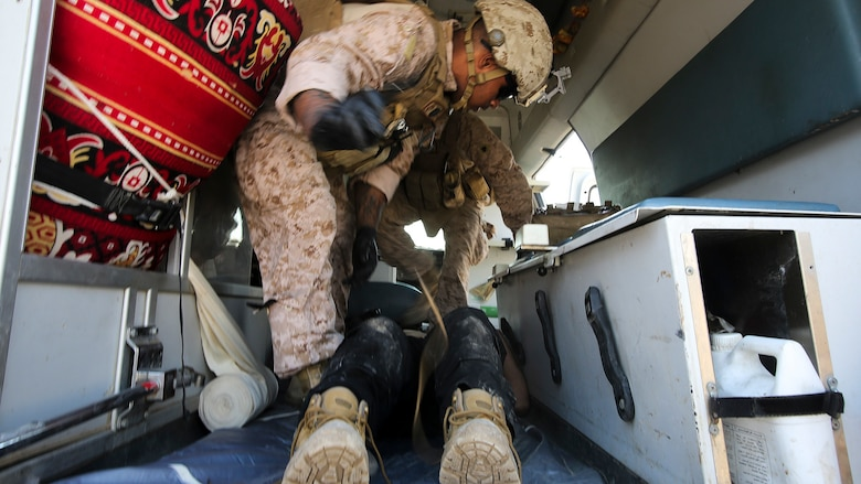 """U.S. Navy Seaman Apprentice Mikail Garib, a hospitalman with Company B, 1st Battalion, 7th Marine Regiment, Special Purpose Marine Air Ground Task Force – Crisis Response – Central Command, treats an Iraqi soldier for combat-related injuries at Al Taqaddum, Iraq, Nov. 28, 2015. Wounded Iraqi soldiers are occasionally transported from battlefields in Ramadi and Fallujah, Iraq, to Al Taqaddum to receive medical treatment from U.S. personnel. U.S. Navy corpsmen with """"Bravo"""" Company, 1st Bn., 7th Marines, are the first responders to attend to the casualties. U.S. Marines and sailors with SPMAGTF-CR-CC are currently deployed in support of Combined Joint Task Force - Operation Inherent Resolve, which focuses on defeating the Islamic State of Iraq and Levant in the U.S. Central Command area of responsibility."""