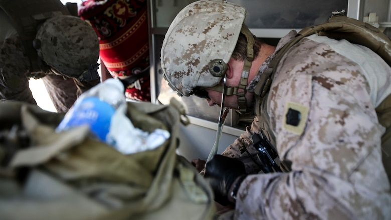 """U.S. Navy Petty Officer 3rd Class Bryan Rileysilva, a hospitalman with Company B, 1st Battalion, 7th Marine Regiment, Special Purpose Marine Air Ground Task Force – Crisis Response – Central Command, treats an Iraqi soldier for combat-related injuries at Al Taqaddum, Iraq, Nov. 28, 2015. Wounded Iraqi soldiers are occacionally transported from battlefields in Ramadi and Fallujah, Iraq, to Al Taqaddum to receive medical treatment from U.S. personnel. U.S. Navy corpsmen with """"Bravo"""" Company, 1st Bn., 7th Marines, are the first responders to attend to the casualties. U.S. Marines and sailors with SPMAGTF-CR-CC are currently deployed in support of Combined Joint Task Force - Operation Inherent Resolve, which focuses on defeating the Islamic State of Iraq and Levant in the U.S. Central Command area of responsibility."""
