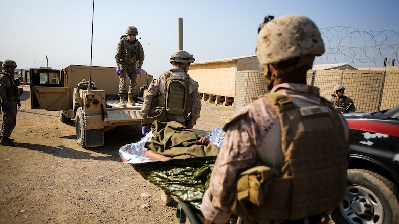 """U.S. Navy corpsmen with Company B, 1st Battalion, 7th Marine Regiment, Special Purpose Marine Air Ground Task Force – Crisis Response – Central Command, and a member of the U.S. Army 772nd Forward Surgical Team, attached to Task Force Al Taqaddum, aid an Iraqi soldier that sustained combat-related injuries, Iraq, Nov. 28, 2015. Wounded Iraqi soldiers are occasionally transported from battlefields in Ramadi and Fallujah, Iraq, to Al Taqaddum to receive medical treatment from U.S. personnel. U.S. Navy corpsmen with """"Bravo"""" Company, 1st Bn., 7th Marines, are the first responders to attend to the casualties. U.S. Marines and Sailors with SPMAGTF-CR-CC are currently deployed in support of Combined Joint Task Force - Operation Inherent Resolve, which focuses on defeating the Islamic State of Iraq and Levant and the threat they pose to Iraq, Syria, the region and the wider international community."""