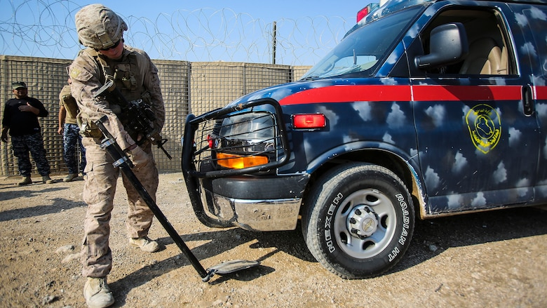 """A U.S. Marine with Company B, 1st Battalion, 7th Marine Regiment, Special Purpose Marine Air Ground Task Force – Crisis Response – Central Command, searches an ambulance carrying an injured Iraqi soldier at Al Taqaddum, Iraq, Nov. 28, 2015. Wounded Iraqi soldiers are occasionally transported from battlefields in Ramadi and Fallujah, Iraq, to Al Taqaddum to receive medical treatment from U.S. personnel. U.S. Navy with """"Bravo"""" Company, 1st Bn., 7th Marines, are the first responders to attend to the casualties."""