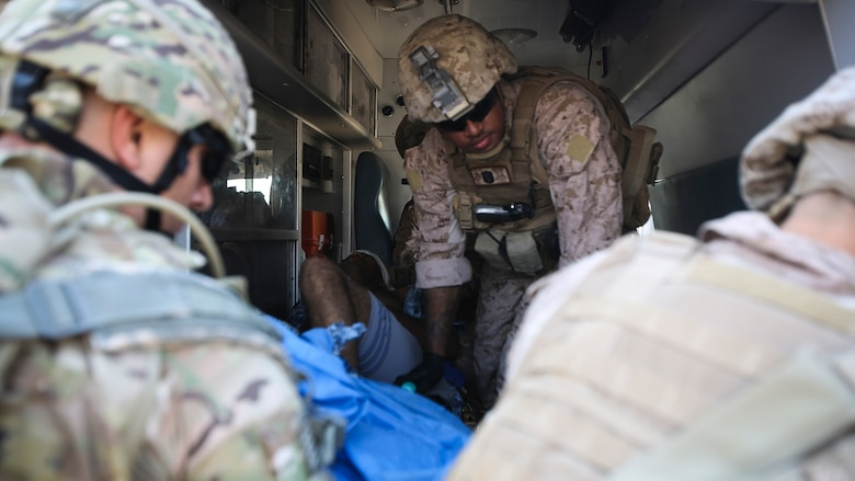 """U.S. Navy Seaman Apprentice Mikail Garib, a hospitalman with Company B, 1st Battalion, 7th Marine Regiment, Special Purpose Marine Air Ground Task Force – Crisis Response – Central Command, prepares an Iraqi soldier with combat-related injuries for transport into the 115th Combat Support Hospital at Al Taqaddum, Iraq, Nov. 28, 2015. Wounded Iraqi soldiers are occasionally transported from battlefields in Ramadi and Fallujah, Iraq, to Al Taqaddum to receive medical treatment from U.S. personnel. U.S. Navy corpsmen with """"Bravo"""" Company, 1st Bn., 7th Marines, are the first responders to attend to the casualties. U.S. Marines and sailors with SPMAGTF-CR-CC are currently deployed in support of Combined Joint Task Force - Operation Inherent Resolve, which focuses on defeating the Islamic State of Iraq and Levant in the U.S. Central Command area of responsibility."""