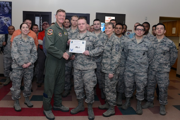 "Senior Airman Steven Lowrance, center, 47th Security Forces Squadron vehicle control officer, poses with Col. Thomas Shank, left, 47th Flying Training Wing commander, and Chief Master Sgt. Teresa Clapper, 47th FTW command chief, after accepting the ""XLer of the Week"" award, here, Dec. 2, 2015. The XLer is a weekly award chosen by wing leadership and is presented to those who consistently make outstanding contributions to their unit and Laughlin. (U.S. Air Force photo by Senior Airman Jimmie D. Pike)"